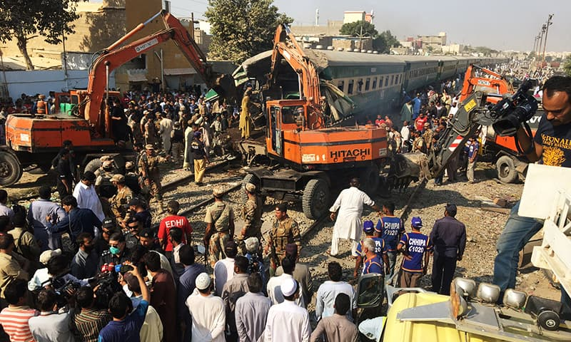 Rescuers workers use heavy machinery on the car of a train.— Reuters