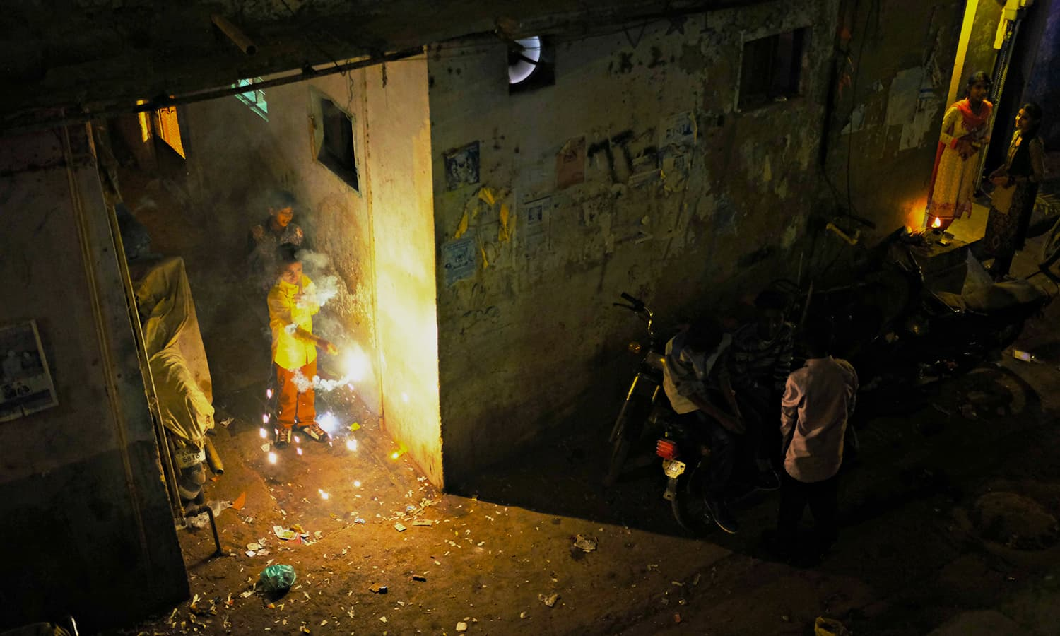 A child lights up sparkles in front of his house in Narayanpura.