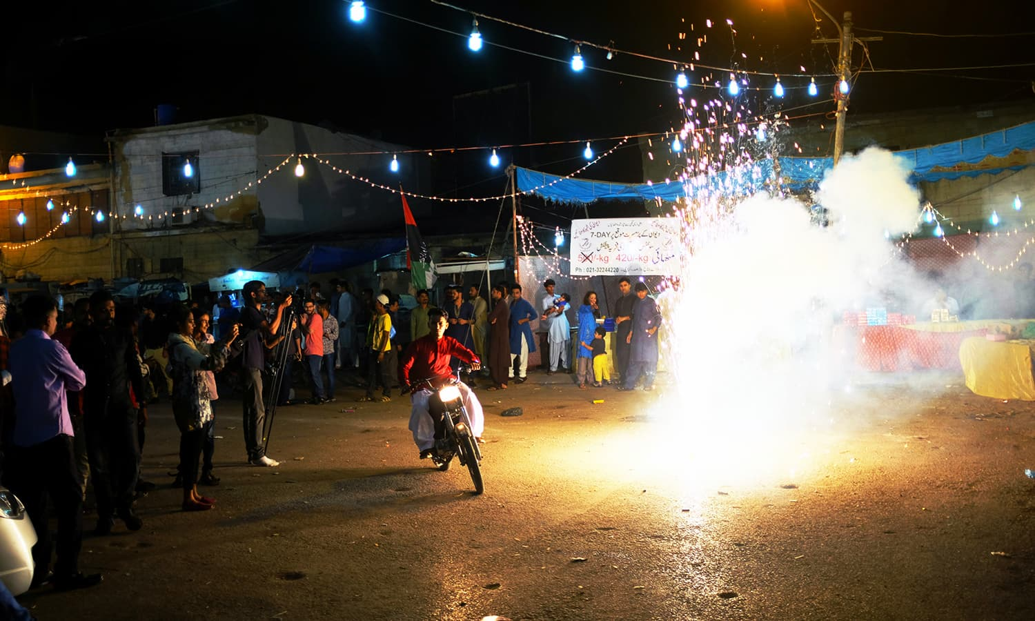 A motorcycle rider passes right by a firecracker.