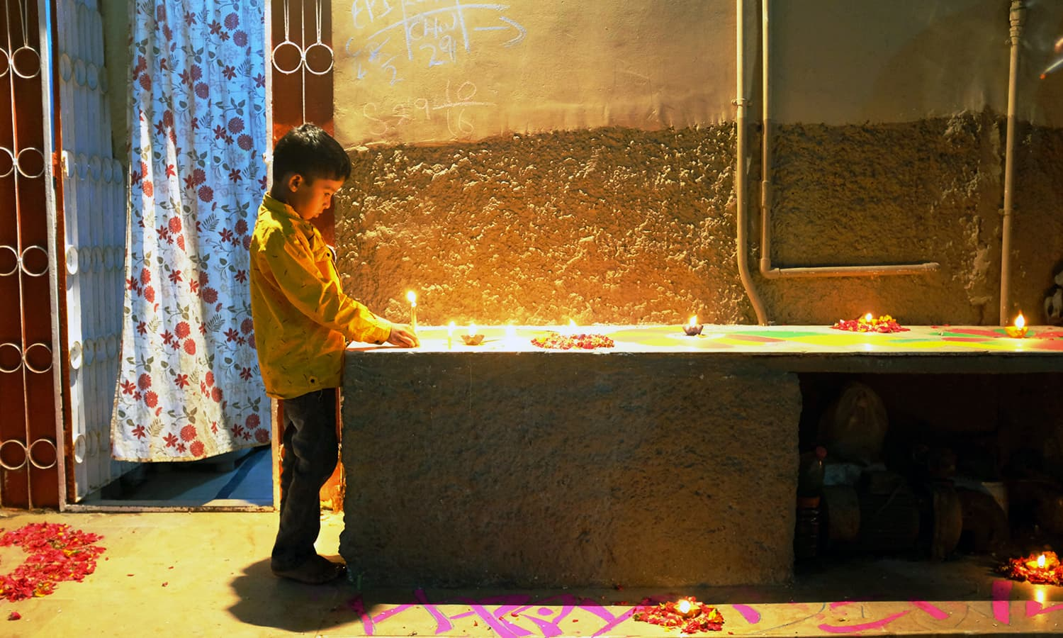 A child lights a candle outside his house.