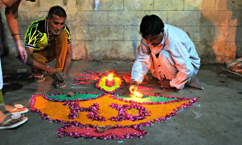 People making rangoli with petals.
