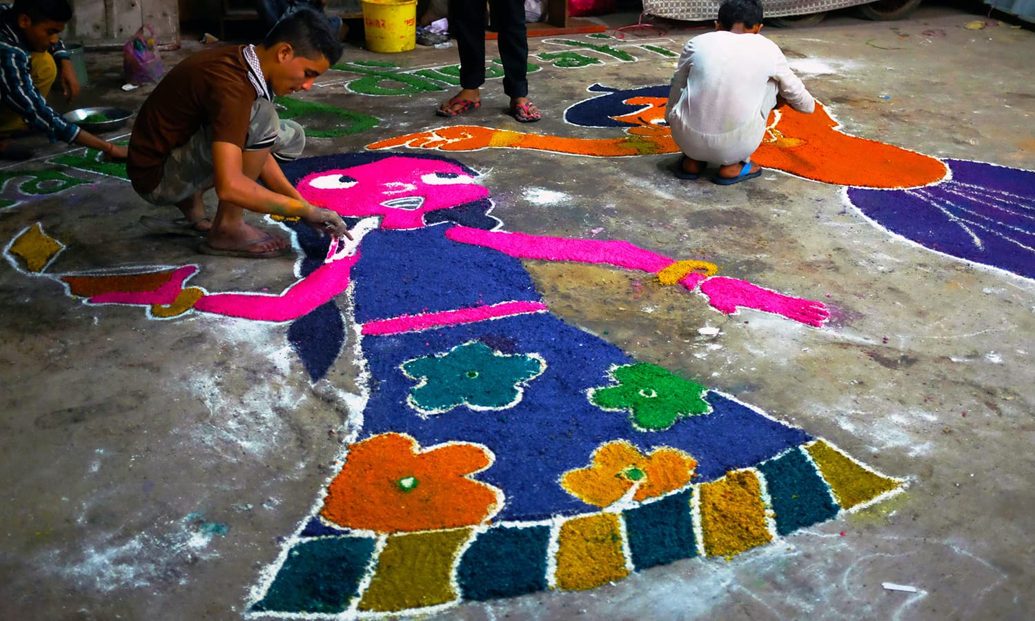 A young man busy creating a colourful design in one of the streets behind Shri Swaminarayan.