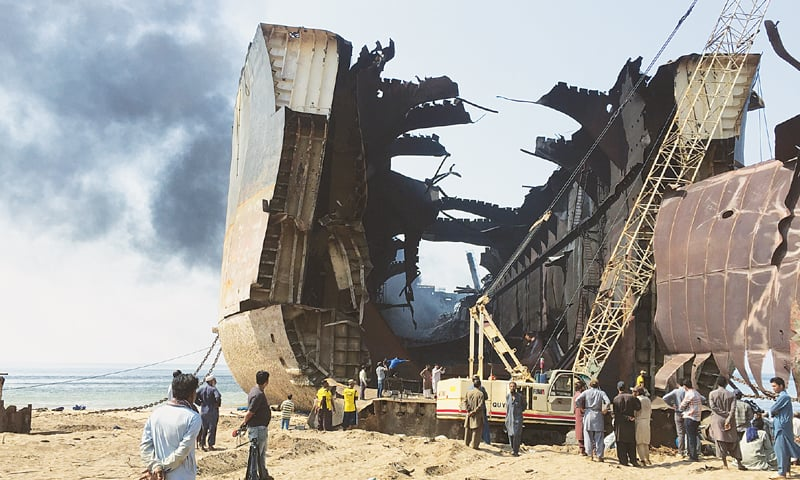 Edhi volunteers and labourers from other ship-breaking companies look on as a crane brings down workers trying to retrieve bodies from the vessel.—Photo by writer
