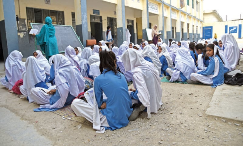 Girls attend a class in the courtyard and have to sit on dusty rugs.— Photo by Khurram Amin