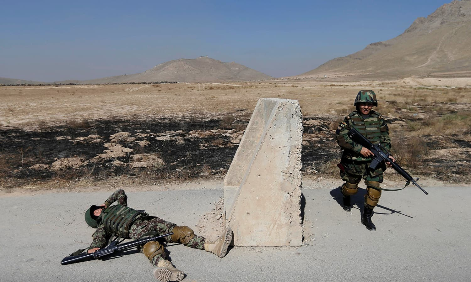 Afghan soldier Tamana, 19 (L), and commander for female soldiers Lieutenant Colonel Cobra Tanha, 45 (R), simulate an injury during a training exercise at the Kabul Military Training Centre (KMTC) in Kabul─Reuters