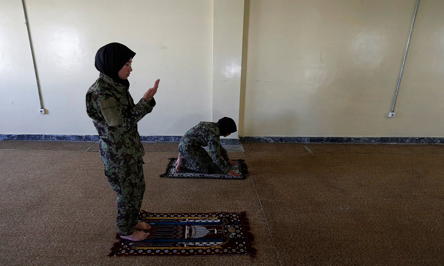Female soldier Aghama Dehqanyar, 19 (L), prays inside a mosque at the Kabul Military Training Centre (KMTC) in Kabul─Reuters