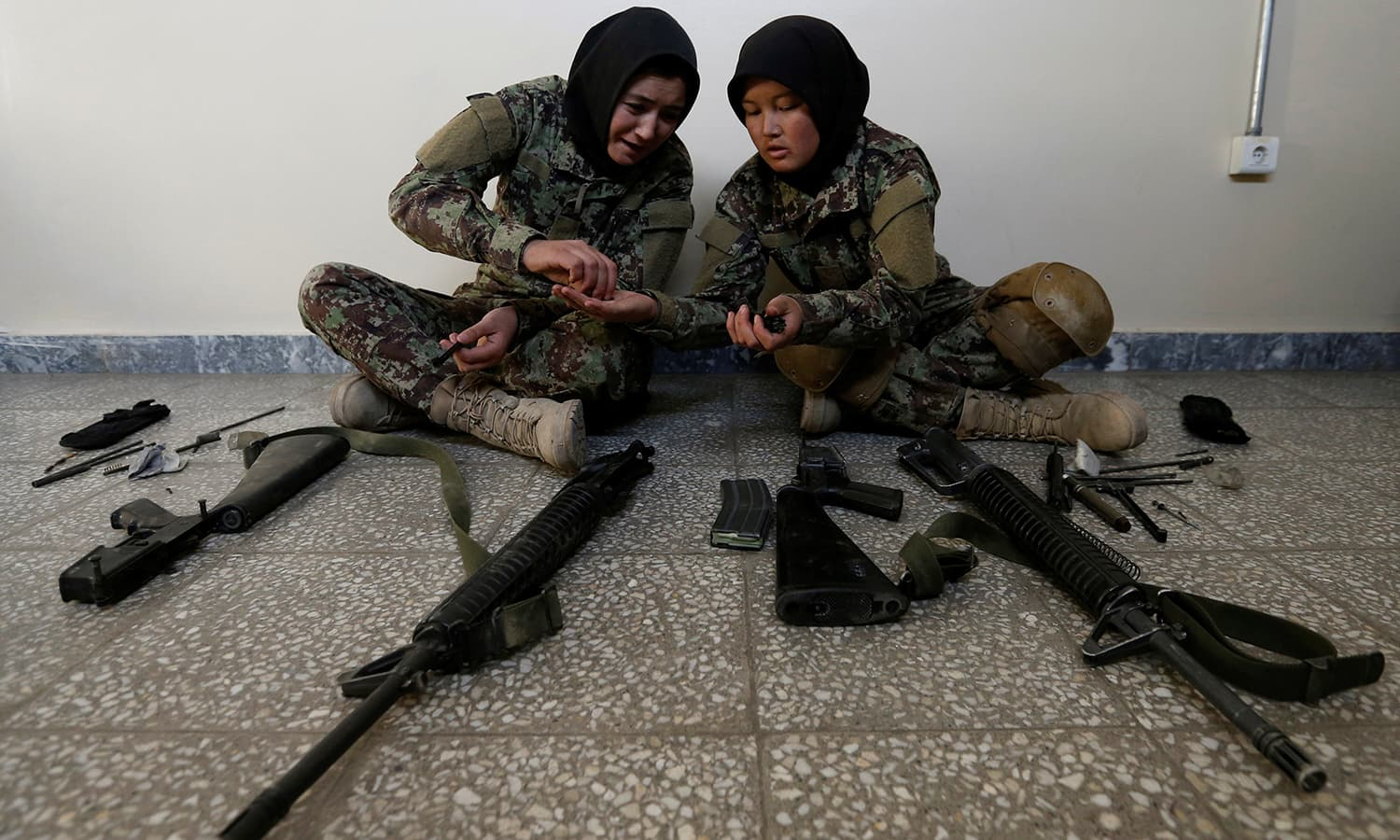 Female soldiers Karima Mohamadi, 21 (L), and Tamana, 19 (R), from the Afghan National Army (ANA) clean their weapons at the Kabul Military Training Centre (KMTC) in Kabul─Reuters.