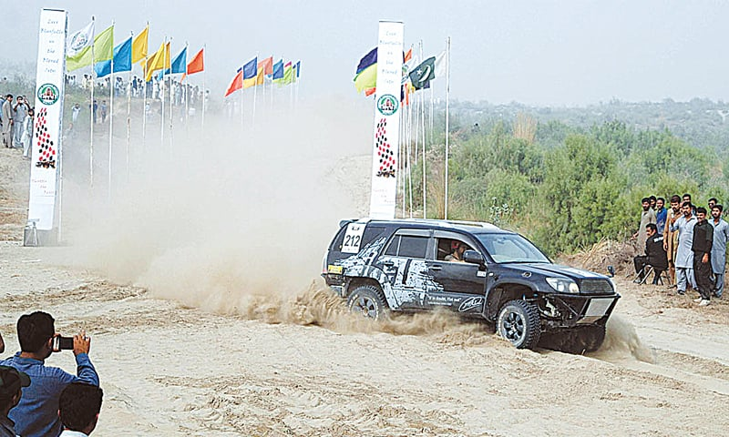 MUZAFFARGARH: A vehicle taking part in the jeep rally drives past spectators on Saturday.—APP