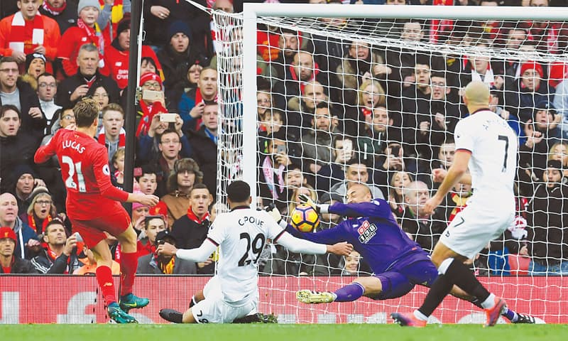 LIVERPOOL: Watford goalkeeper Heurelho Gomes makes a save from Liverpool's Lucas Leiva (L) during their Premier League match at Anfield on Sunday.—AFP