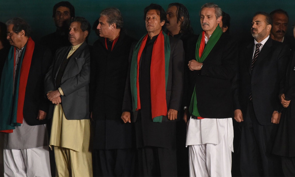 Imran Khan, flanked by Shah Mehmood Qureshi (L) and Jahangir Tareen (R), at a rally in Islamabad | AFP