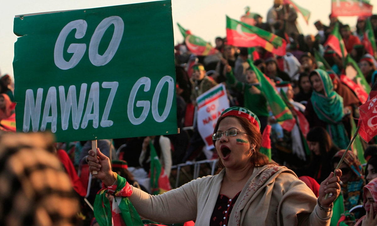 A supporter holds a sign against Prime Minister Nawaz Sharif during a rally in Islamabad | Reuters