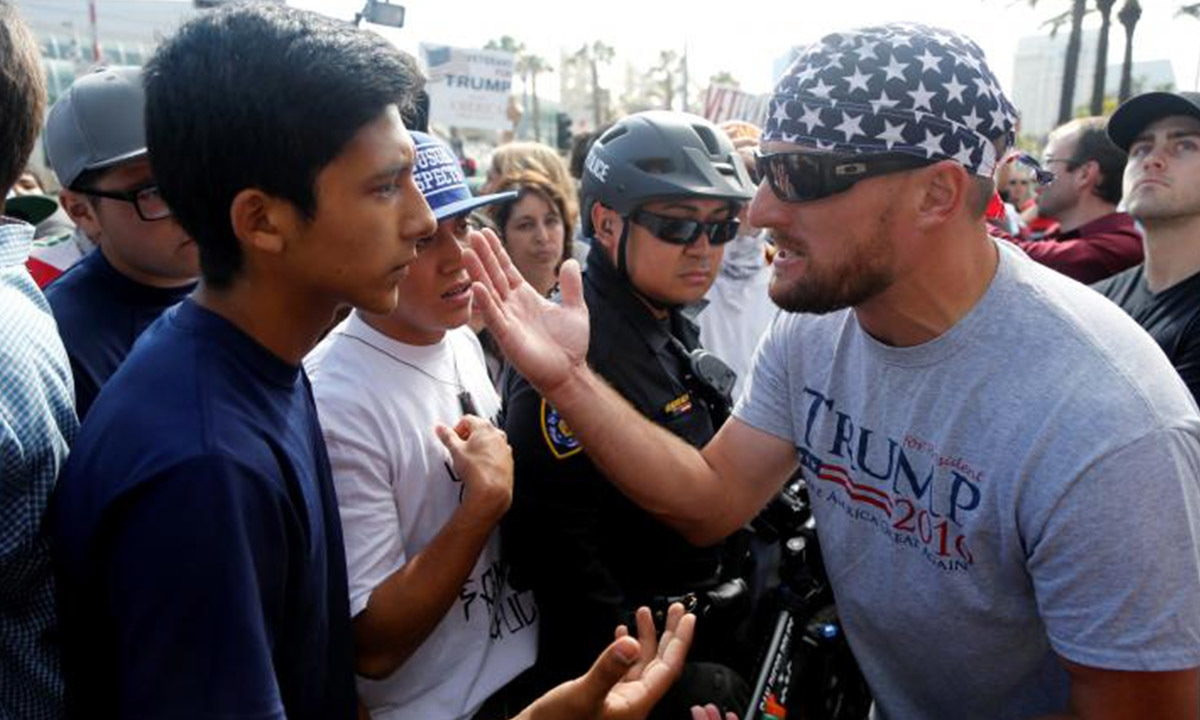 An anti-Trump protester (L) and a Trump supporter (R) argue during protests against Trump in May | Reuters
