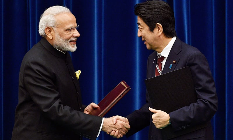 India's Prime Minister Narendra Modi and his Japanese counterpart Shinzo Abe shake hands. -AFP