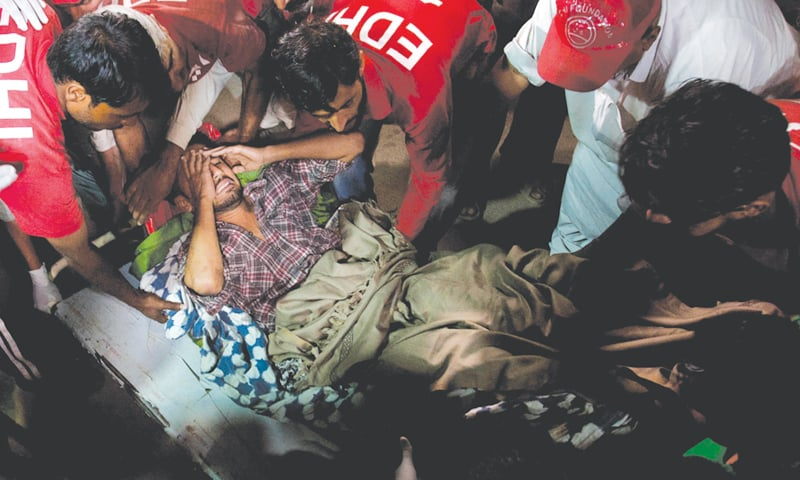 HUB: Rescue workers and volunteers shift a victim of the suicide attack at the Shah Noorani shrine from an ambulance to a stretcher at a hospital here on Saturday night.—AP