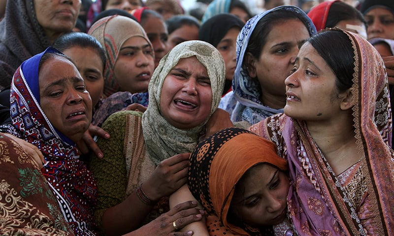 Women mourn for their family members who were killed in the bomb blast at the Shah Noorani shrine prior to funeral prayers in Karachi. ─ AP