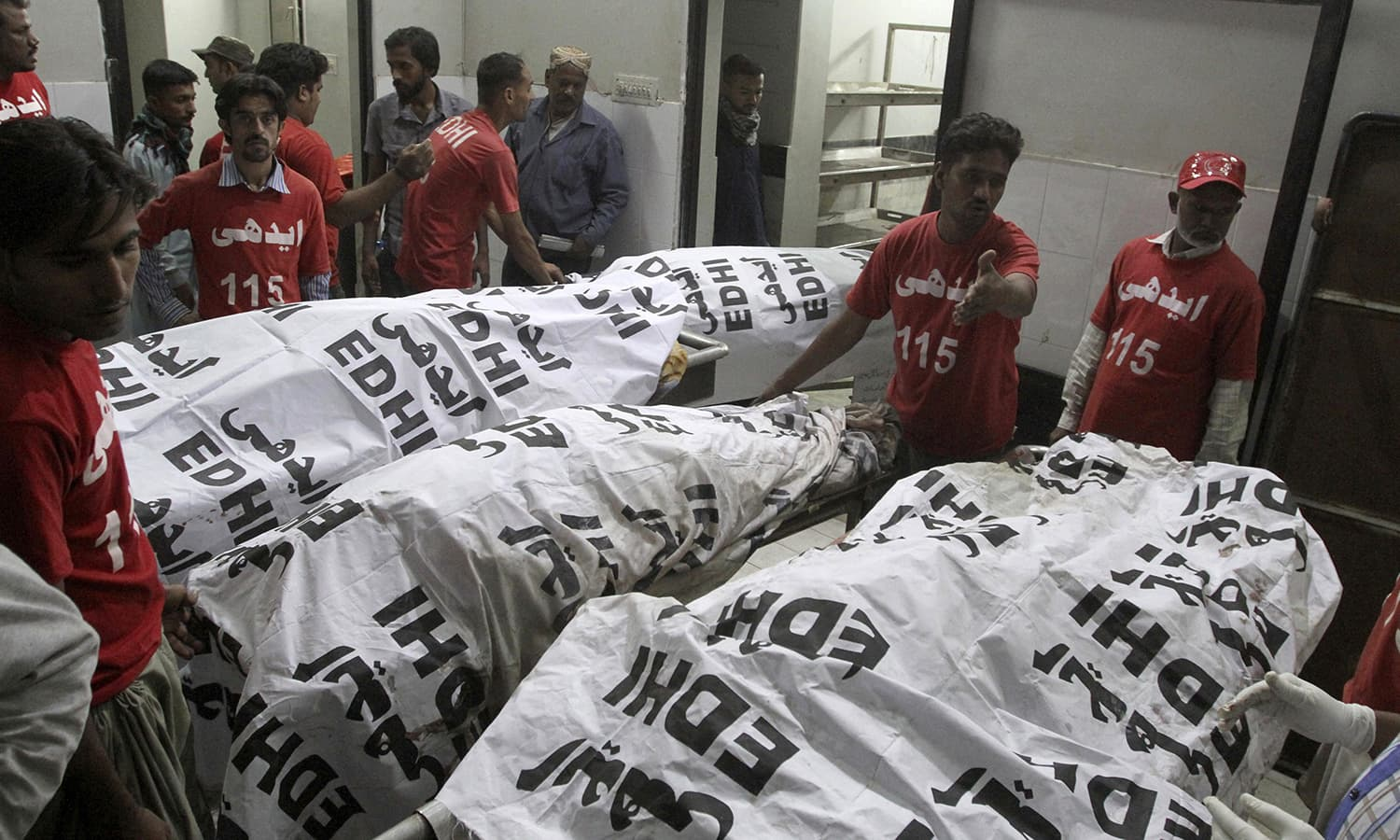 Volunteers arrange bodies of the victims of shrine bomb blast at a morgue in Karachi. ─ AP