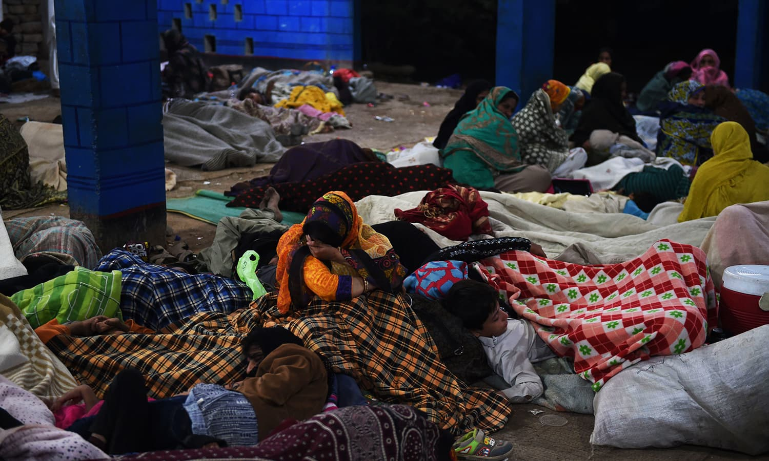 Devotees take shelter after a suicide bomb attack near the shrine of Sufi saint Shah Noorani. ─ AFP