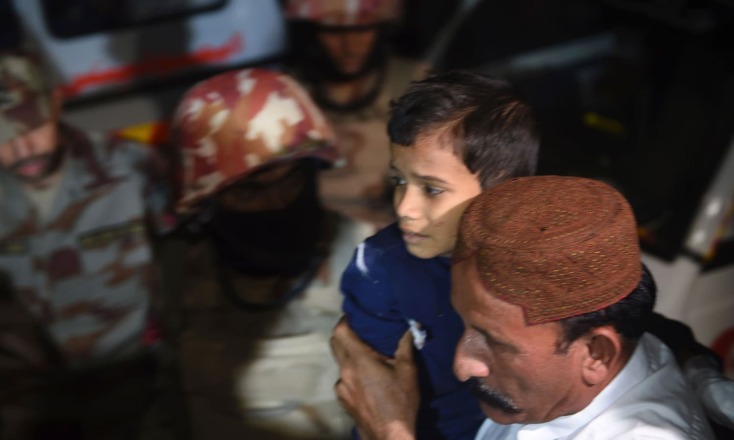 A man carries a boy injured after a bomb blast at a hospital in the Hub district. ─ AFP