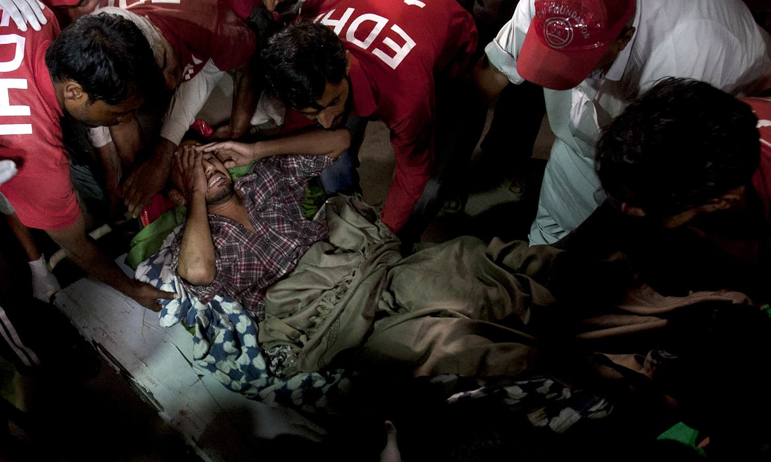 Pakistani rescue workers and volunteers unload an injured victim of bomb blast at a Sufi shrine. ─ AP