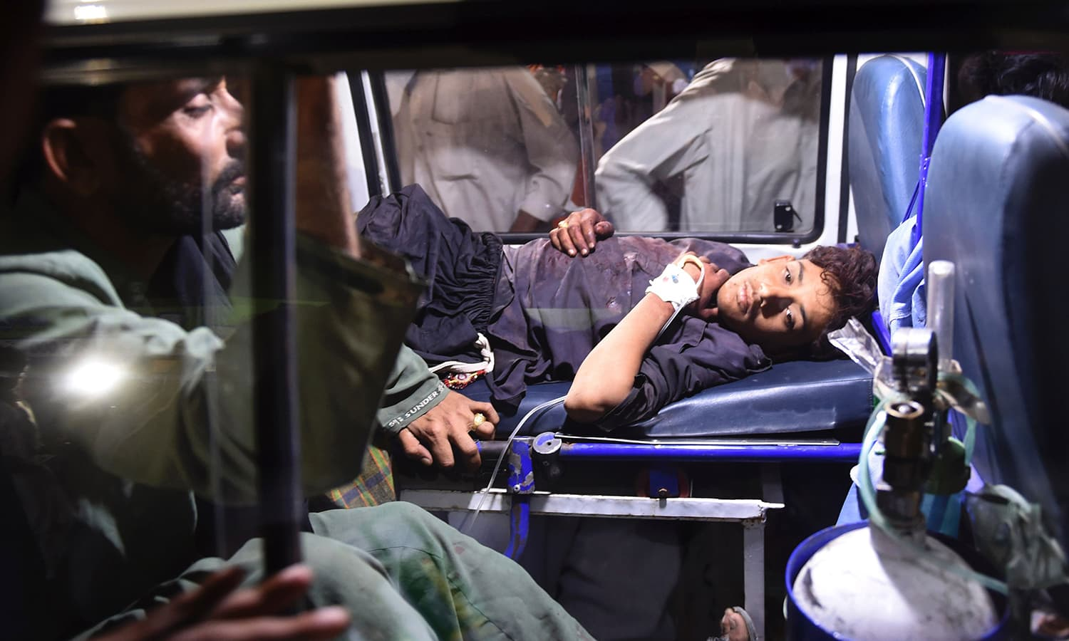 Rescuers transport an injured person to a hospital in Karachi. ─ AFP