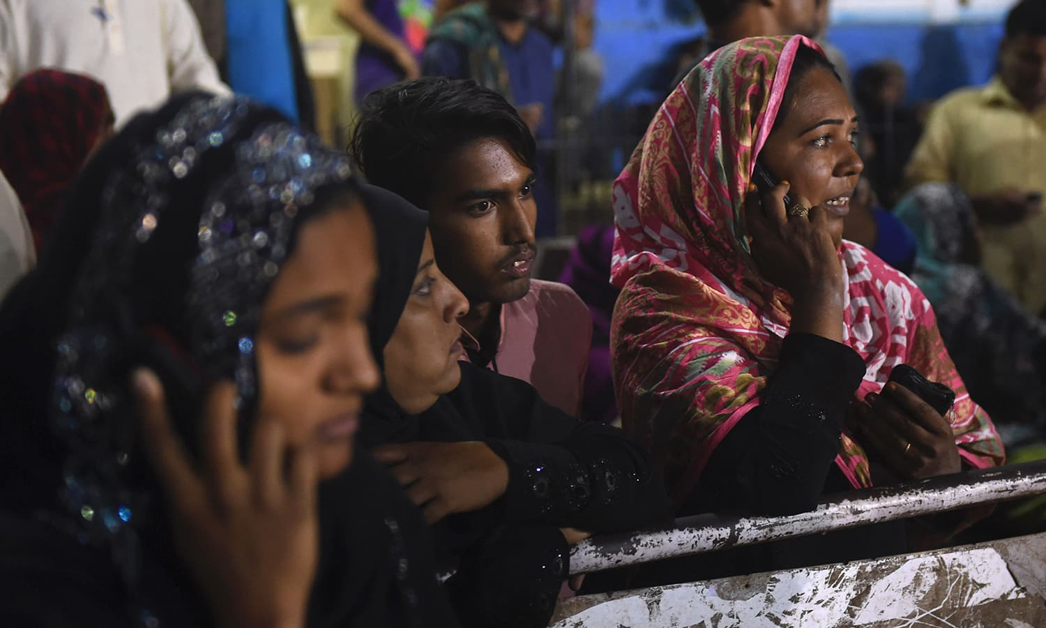 Women talk on phones while gathering outside of a mortuary in Karachi. ─ AFP