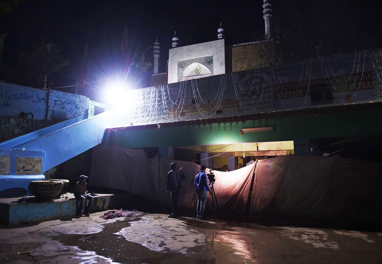 A Pakistani camera man (C) takes video of the suicide blast site. ─ AFP