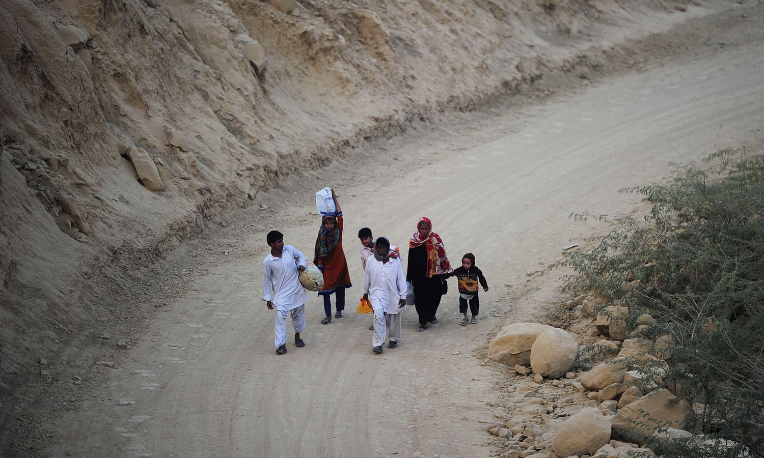 Devotees walk back home from the shrine of Sufi saint Shah Noorani following the suicide bomb attack. ─ AFP