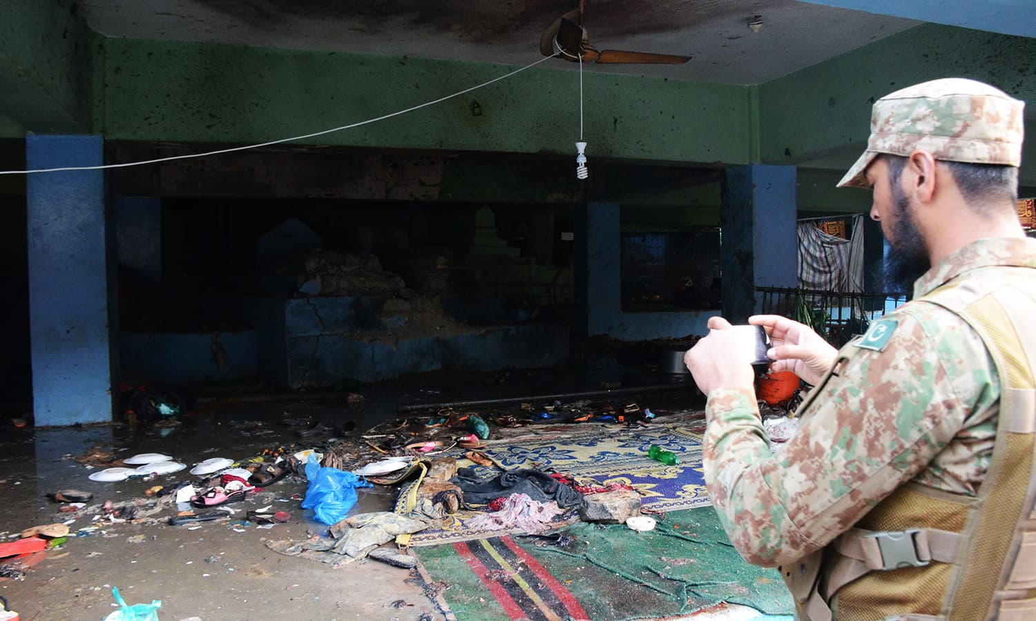 A Pakistan Army soldier takes pictures of the suicide blast site. ─ AFP