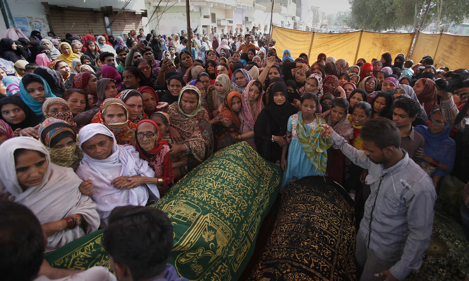 Women gather around the coffins of the victims of the bomb blast. ─ AP