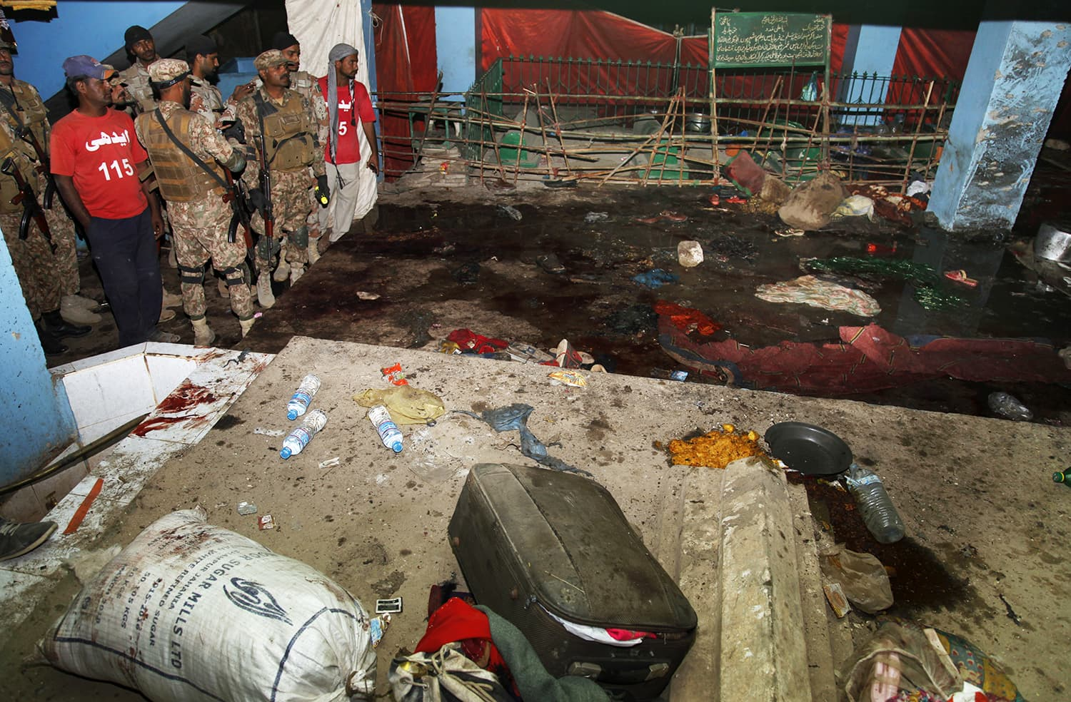 Pakistani Army troops and rescue workers examine the site of the bomb blast. ─ AP