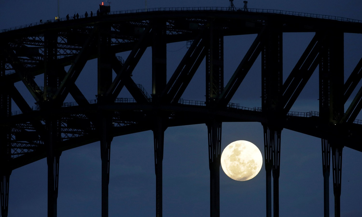 Participants in a Sydney Harbour Bridge Climb walk across the western span of the famous Australian landmark as the supermoon rises after sunset. ─Reuters