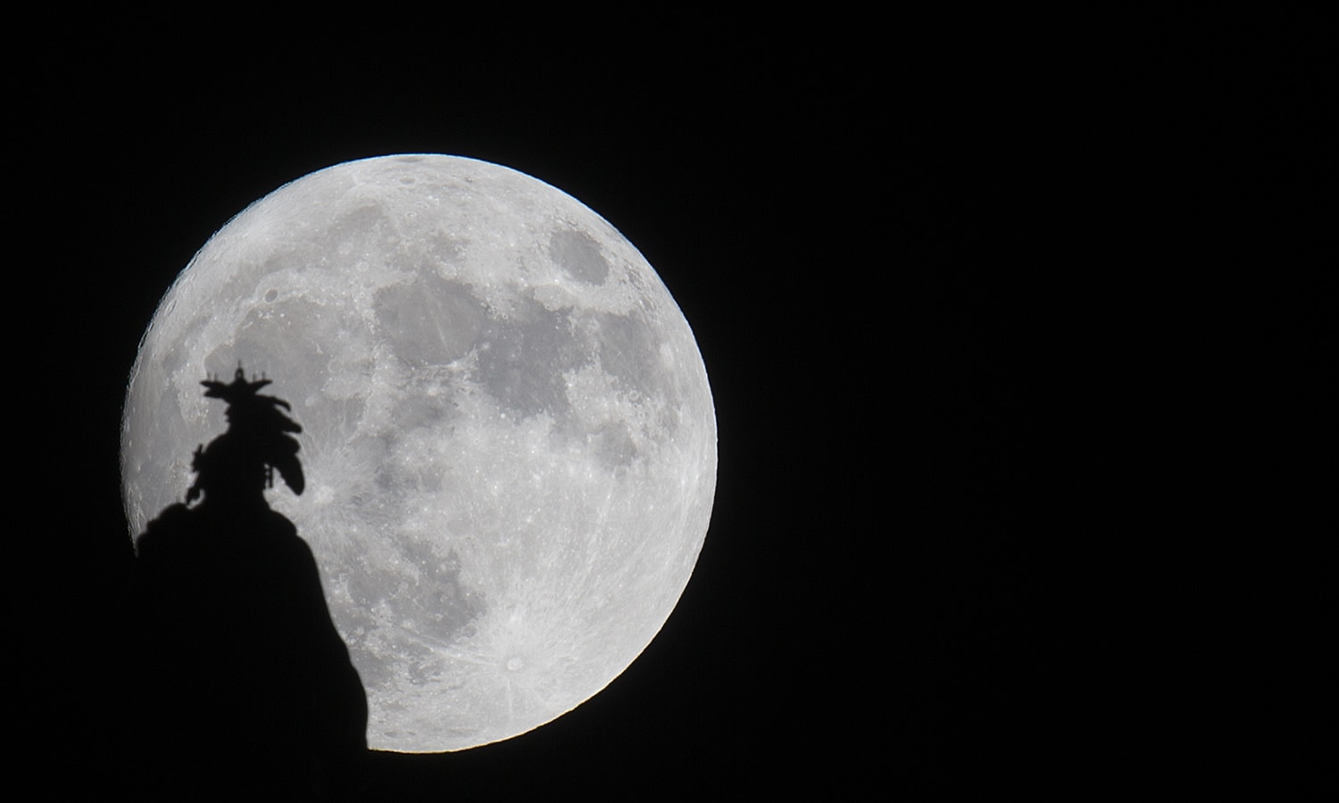 A supermoon rises over the Statue of Freedom on the Capitol dome in Washington, DC November. ─AFP