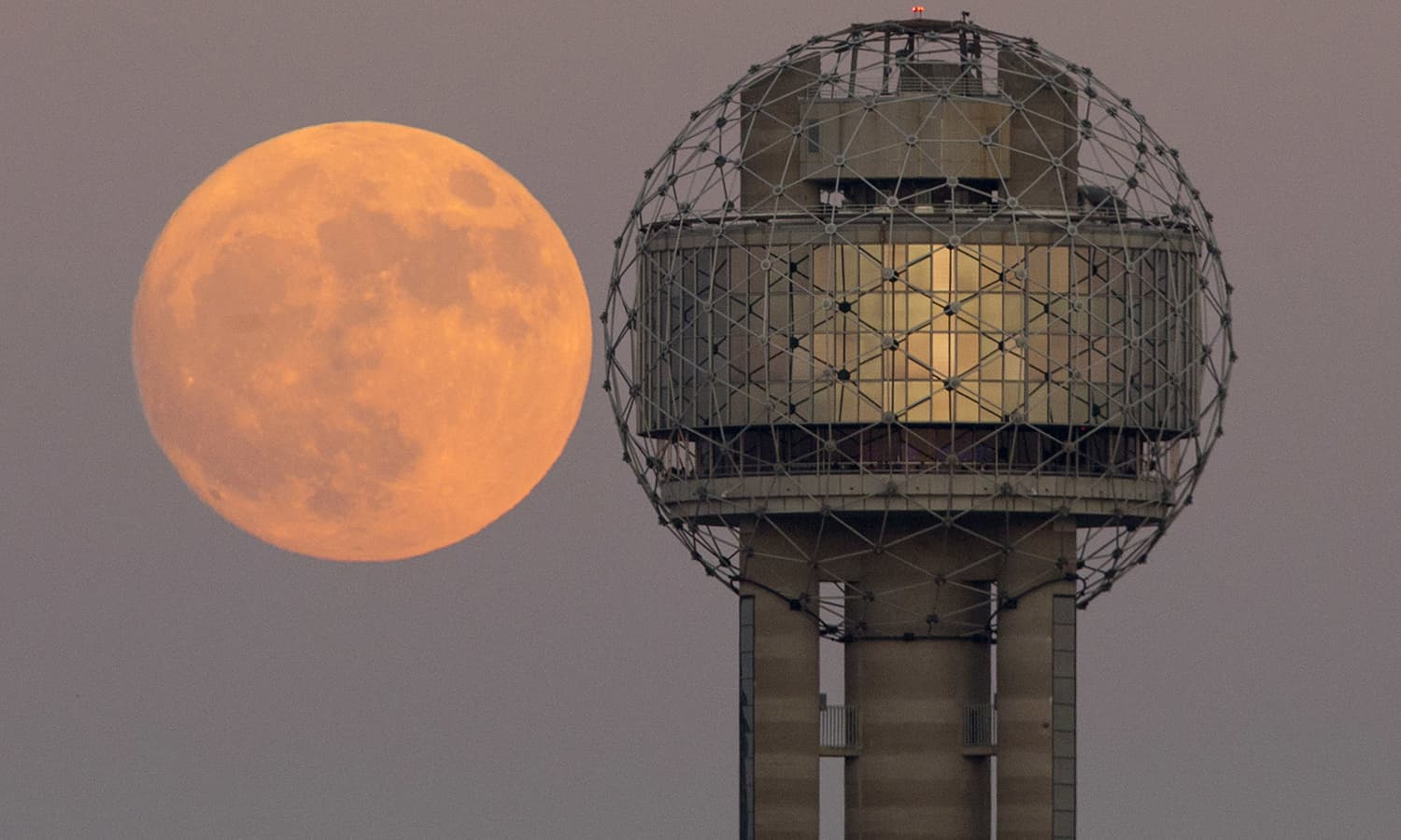 The moon rises behind Reunion Tower in downtown Dallas. ─AP