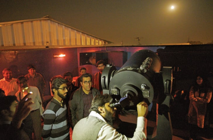 Students look at the supermoon from a telescope in Islamabad on Monday. — Photo by Tanveer Shahzad