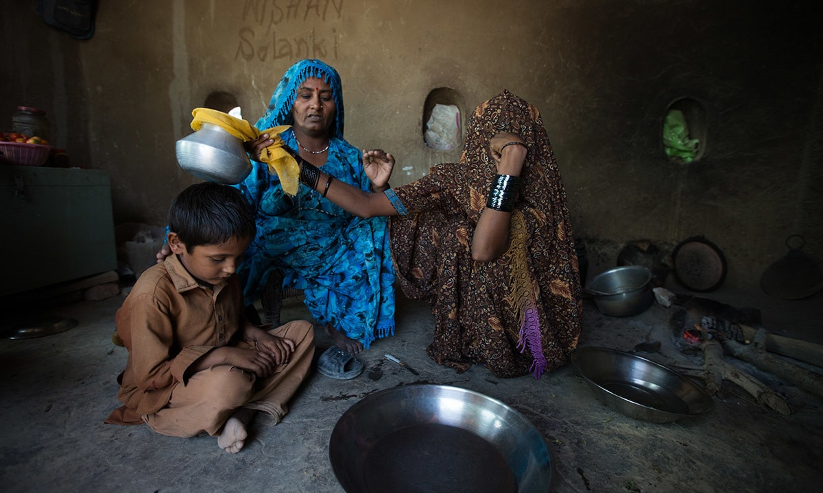 Lilavati holds an aluminium pot containing dried chillies, coal and salt over her three-year-old son Kishore's head to protect him from evil spirits