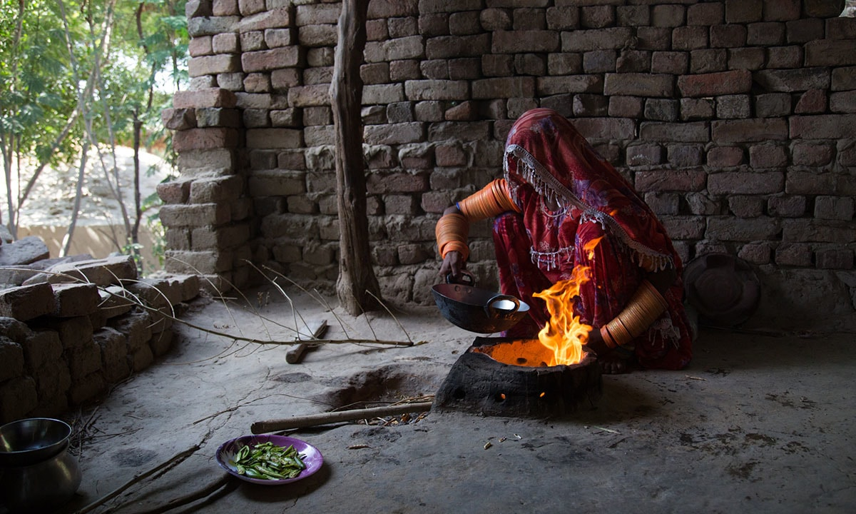 A woman prepares fried chillies for her family after a day in the field