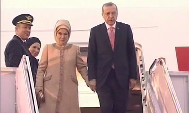 Turkish President Erdogan exits his plane alongside his wife. ─ DawnNews