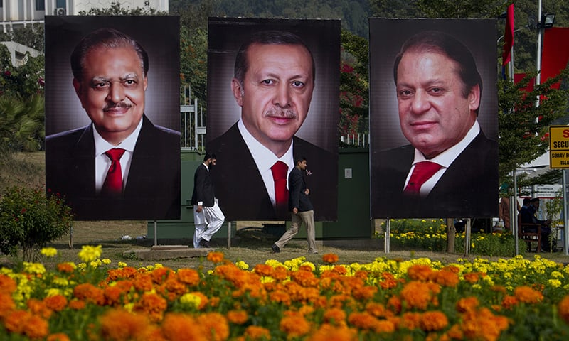 People walk pasts billboards showing portraits of President Erdogan, President Mamnoon and PM to welcome Erdogan. ─AP