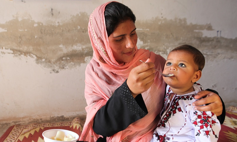 An 18-month old child is fed by his mother in Muzaffargarh.— UNICEF/Pakistan/Giacomo Pirozzi