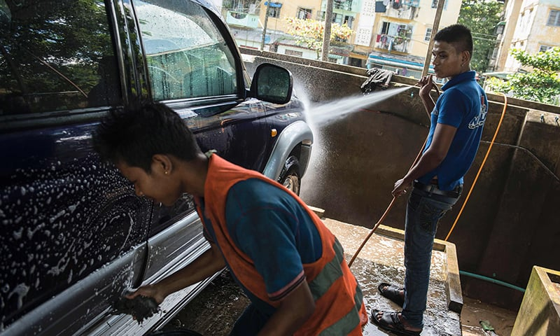 Former Myanmar child soldier, 21-year-old Su Thet Htoo (R) cleans a car at a car wash and repair shop in Yangon. ─AFP
