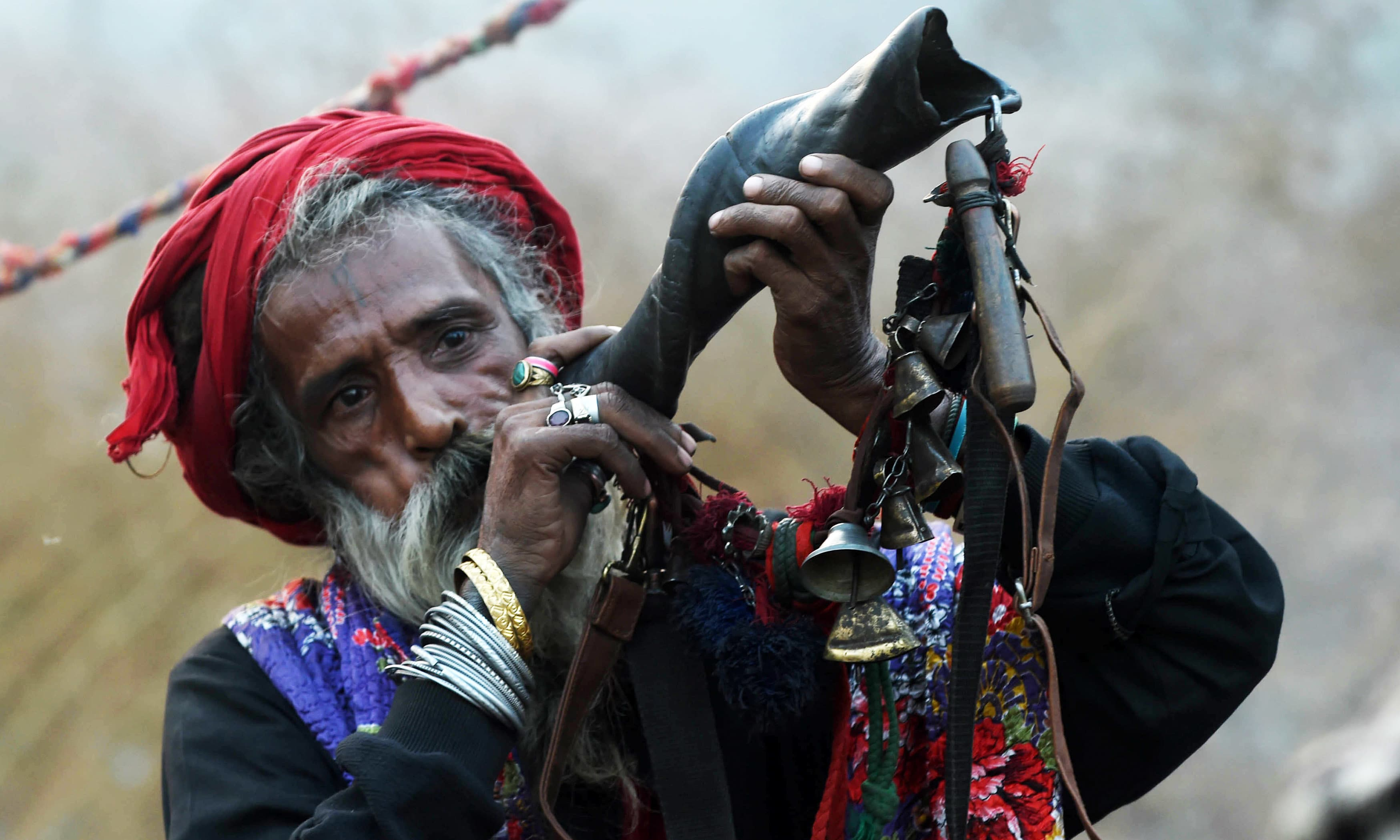 Sufis blow horns outside the Data Darbar. — AFP