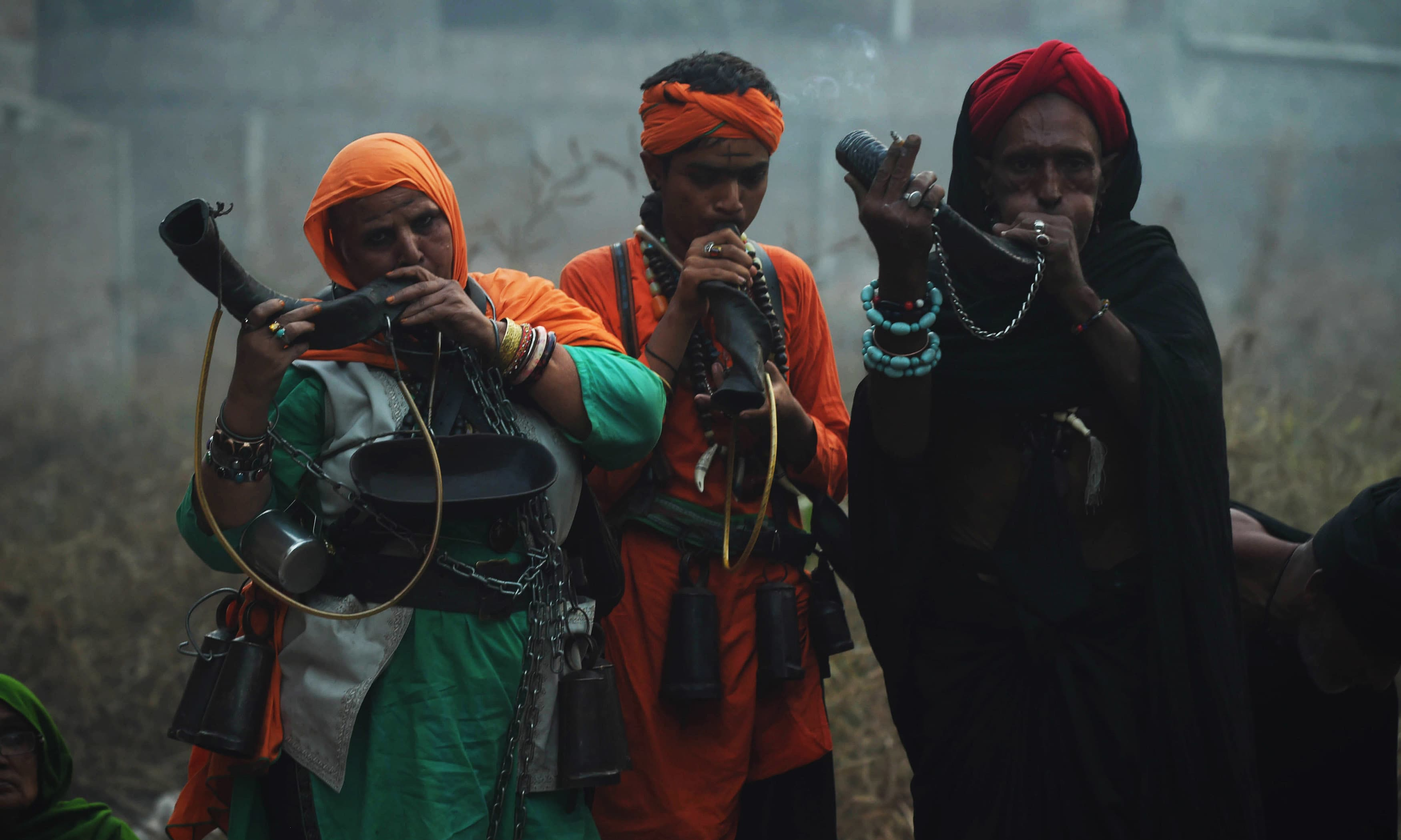 Sufis blow horns outside the Data Darbar to pay homage to Data Ganj Bakhsh.─AFP