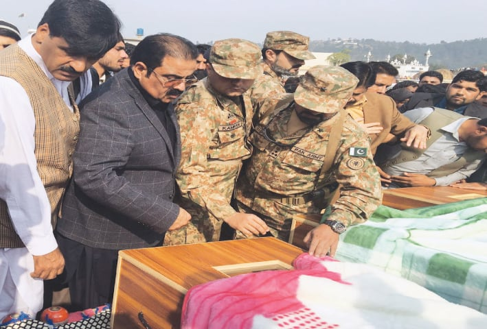 LEADER of Opposition in AJK Legislative Assembly Chaudhry Mohammad Yasin (second left), army officials and local people have a last glimpse of the children killed in Indian shelling before their burial in Singhaal village on Sunday.—Dawn