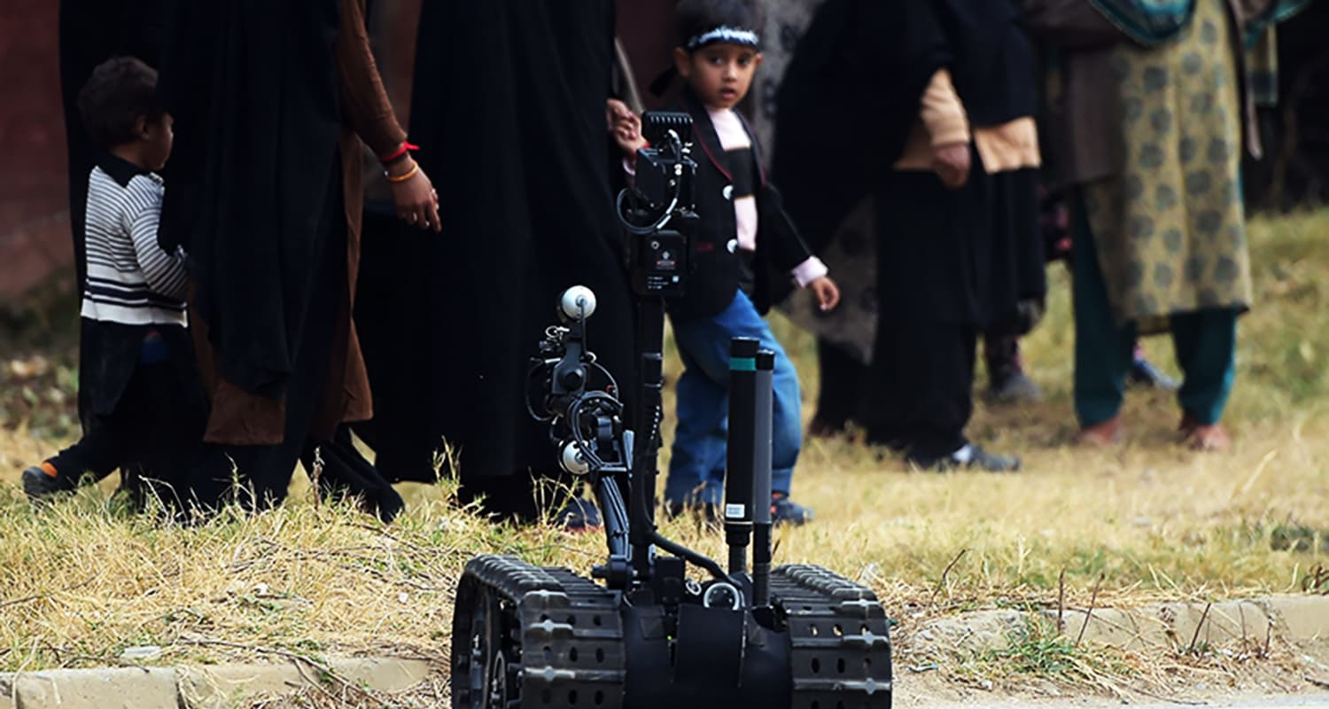 A robot conducts a security sweep of the procession area as a child looks on. — AFP