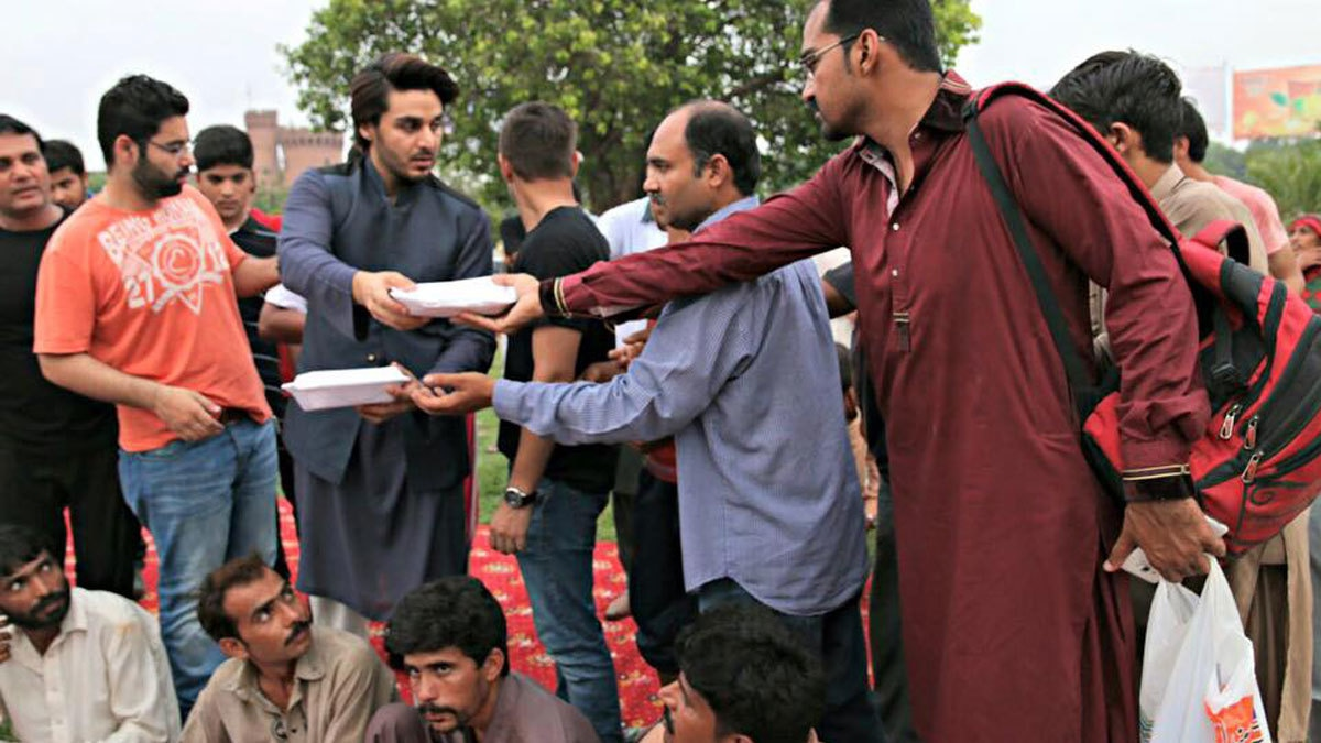 Ahsan Khan helping Rizq distribute food among the less privileged. Photo: Facebook