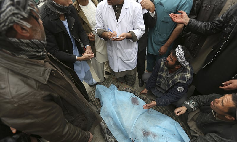Afghans carry the dead body of a man at a hospital after a suicide attack, in Kabul. ─ AP