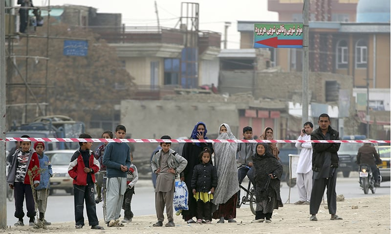 Afghans gather near the Shia Baqir-ul Ulom mosque after a suicide attack inside it in Kabul. ─ AP