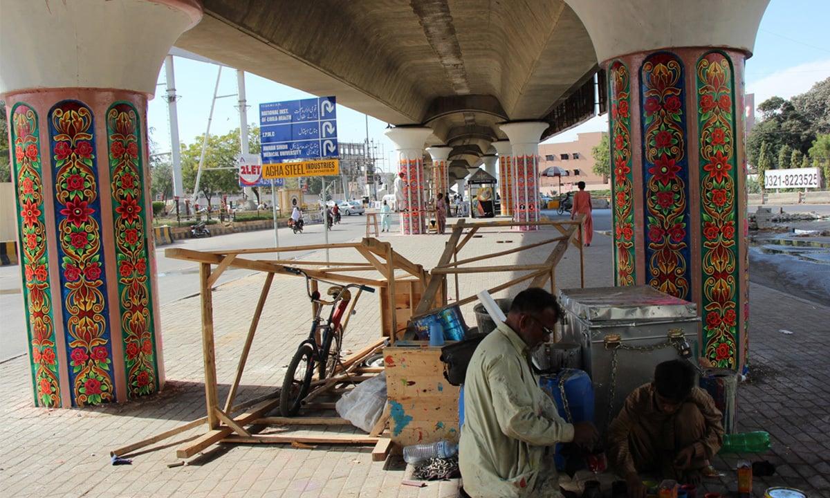 A man paints flower motifs beneath the Jinnah Hospital Flyover in Karachi for IAK   Annie Ali Khan