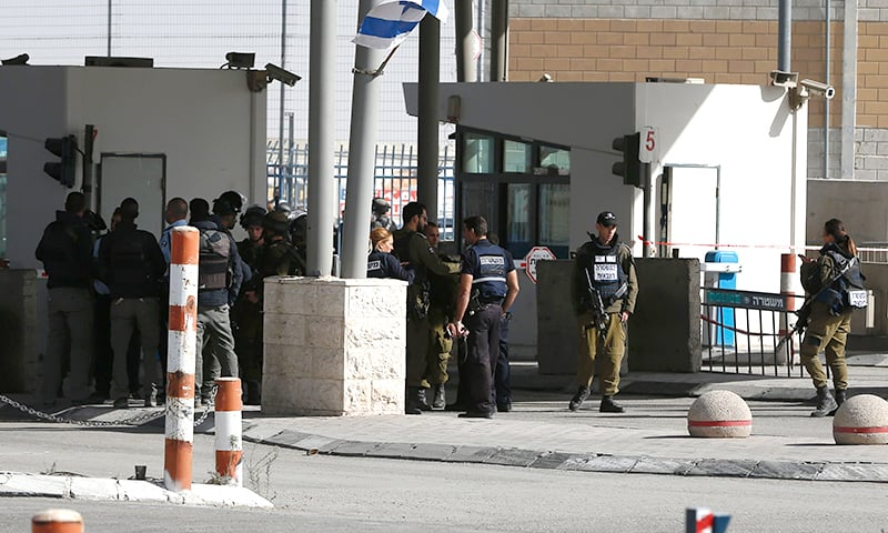 Israeli security forces gather at the site where a Palestinian was shot dead after allegedly walking towards guards wielding a knife at the Qalandia checkpoint crossing between the West Bank city of Ramallah and Israeli-annexed east Jerusalem. ─ AFP