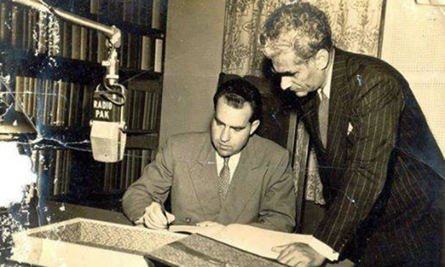 US Vice President John Wayne and a curly-haired Pakistani reviewing an agreement in Karachi in 1958. The US agreed to provide Pakistan economic and military aid but was non-committal about sharing Coca Cola's secret formula. The curly haired Pakistani was very disappointed.
